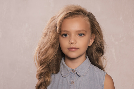 portrait of cute little 8-9 year old girl with blonde hair, wearing jeans jacket, standing against gray background