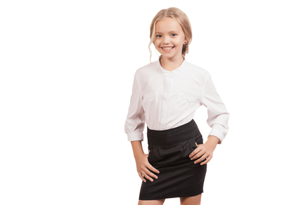 Lovely nine year old schoolgirl in a shirt and a skirt posing isolated on white