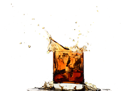 Ice cube falling into whiskey in glass isolated on white