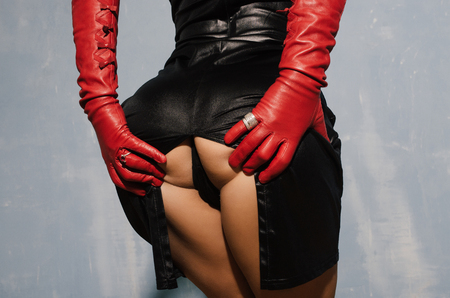 Sexy woman in a dress with a cut back stand in red gloves holding herself in the ass. Stock Photo
