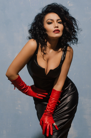 Beautiful model wearing black spandex dress and long red leather gloves.