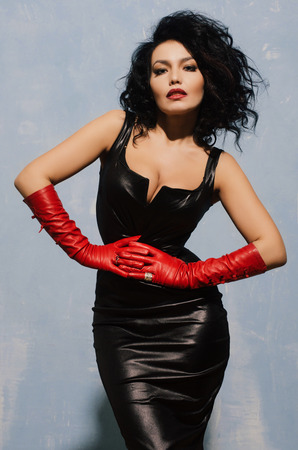 Beautiful adult woman wearing black spandex dress and long red leather gloves. Фото со стока