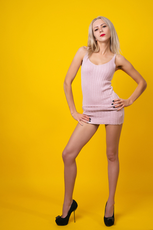 Pretty blonde girl is posing on yellow background wearing pink short dress.