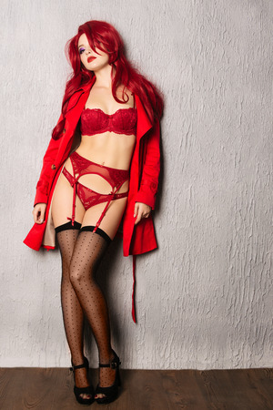 Sensual long-haired redhead woman posing in sexy underwear, stockings, high heels and red cloak, has perfect body