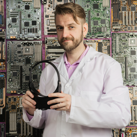 A young electronics engineer stands with a magnifying glass in his hands near the wall of motherboards.