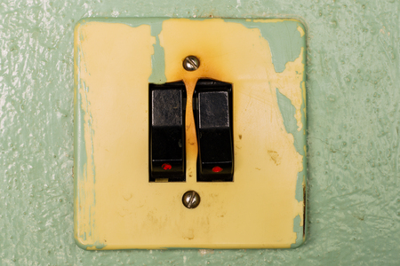 Fused light switch dropped from the green wall. Electrical safety, electric shock. Banco de Imagens