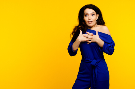 adult surprised woman in blue suit on yellow background.