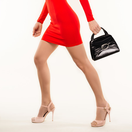 woman in red dress in high heels with hand bag isolated on white