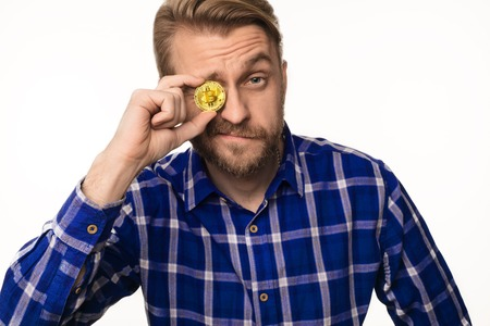 Portrait of a winking man holds a coin bitcoin in front of his eye isolated on white Stock Photo