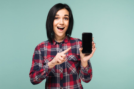 Surprised happy brunette woman in plaid shirt showing blank smartphone screen and pointing on it while looking at the camera with open mouth over teal background - Image