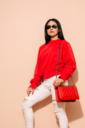 Fashion young woman in white jeans and sweater with red bag clutch in hands near wall