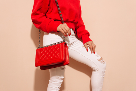 Fashion young woman in white jeans and sweater with red bag clutch in hands near street wall closeup Фото со стока