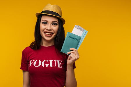 Young smiling excited woman student holding passport boarding pass ticket isolated on yellow background. Education in university college abroad. Air travel flight - Image