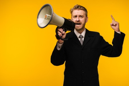 business, people, communication and public announcement concept - angry businessman in suit speaking to megaphone over yellow background - Image