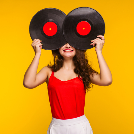 Young smiling woman closing her face with vinyl record discs. Funny DJ concept - Image