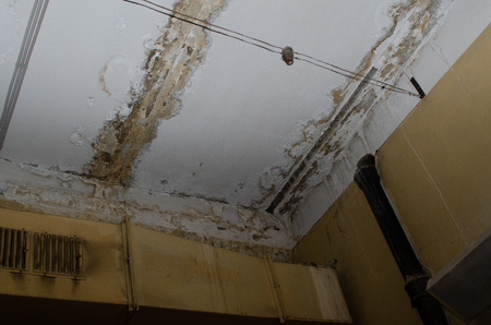 Big wet spots and cracks on the ceiling of the domestic house room after heavy rain and lot of water - Image Stock Photo