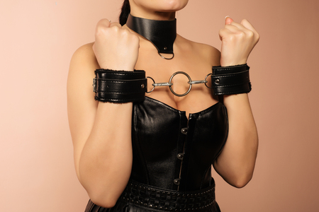 Submissive girl in leather black corset, handcuffs and collar waiting for punishment. - Image Stock Photo