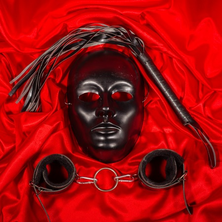 Bondage, kinky adult games, kink and BDSM lifestyle concept with a mask, pair of leather handcuffs, flogger, ball gag and a coller with a leash attached on red silk with copy space