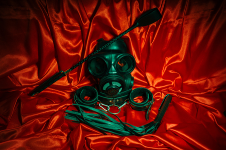 Close up bdsm outfit. Bondage, kinky adult sex games, kink and BDSM lifestyle concept with gas mask, whip, collar, leather handcuffs , lash on red silk with copy space. Stock Photo