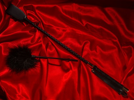 Bondage, kinky adult sex games, kink and BDSM lifestyle concept with a whip, feather stick on red silk with copy space