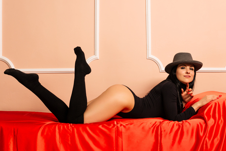Young beautiful woman in hat and black body lying on the red sofa. - Image