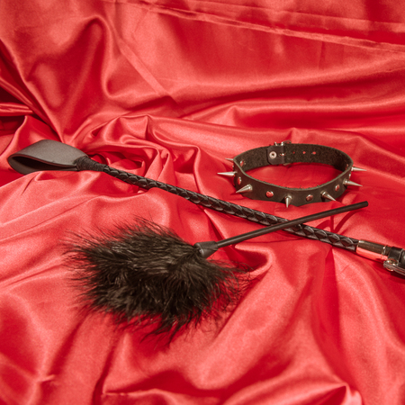 Bondage, kinky adult sex games, kink and BDSM lifestyle concept with a whip, feather stick, collar on red silk with copy space Stock Photo