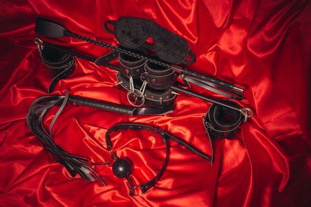 Bondage, kinky adult sex games, kink and BDSM lifestyle concept with a pair of leather handcuffs, flogger, ball gag and a coller with a leash attached on red silk with copy space Banque d'images - 118853970