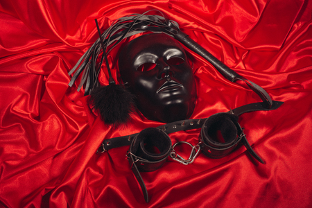 Bondage, kinky adult sex games, kink and BDSM lifestyle concept with a mask, pair of leather handcuffs, flogger, ball gag and a coller with a leash attached on red silk with copy space Banque d'images - 118854211
