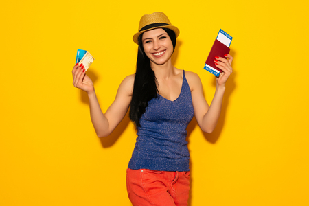 Young smiling excited woman student holding passport boarding pass ticket and credit card isolated on yellow background. Air travel flight - Image Stockfoto