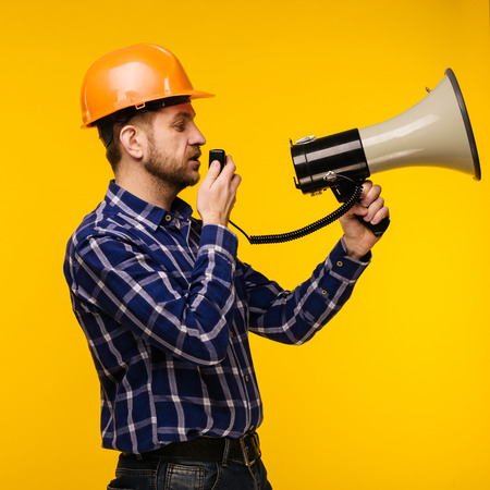 Angry worker man in orange helmet with a megaphone on yellow background - Image