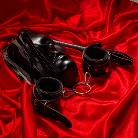 Bondage, kinky adult sex games, kink and BDSM lifestyle concept with a mask, pair of leather handcuffs, flogger, ball gag and a coller with a leash attached on red silk with copy space Banque d'images - 118854273