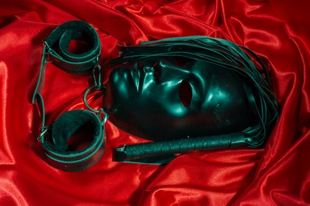 Bondage, kinky adult sex games, kink and BDSM lifestyle concept with a mask, pair of leather handcuffs, flogger, ball gag and a coller with a leash attached on red silk with copy space Banque d'images - 119496519