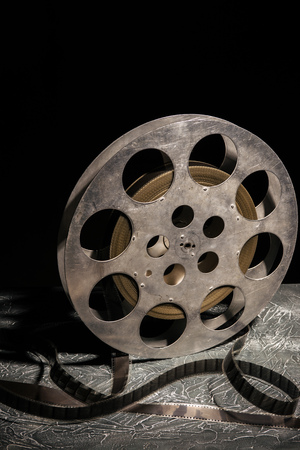 35 mm film reel with dramatic lighting on a dark background - image Archivio Fotografico