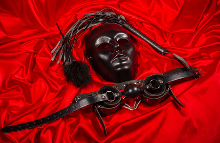 Bondage, kinky adult sex games, kink and BDSM lifestyle concept with a mask, pair of leather handcuffs, flogger, ball gag and a coller with a leash attached on red silk with copy space Banque d'images - 119583104