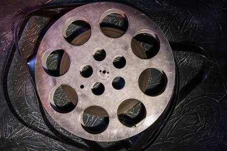 35 mm film reel with dramatic lighting on a dark background - image Stock Photo
