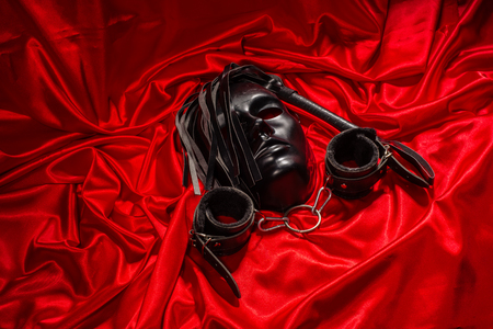 Bondage, kinky adult sex games, kink and BDSM lifestyle concept with a mask, pair of leather handcuffs, flogger, ball gag and a coller with a leash attached on red silk with copy space Stock Photo