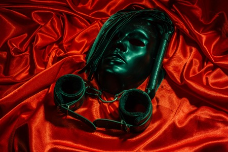 Bondage, kinky adult sex games, kink and BDSM lifestyle concept with a mask, pair of leather handcuffs, flogger, ball gag and a coller with a leash attached on red silk with copy space Banque d'images - 119753542
