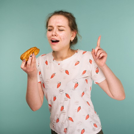 Portrait of pimply teen girl wants to eat eclair cake on blue background