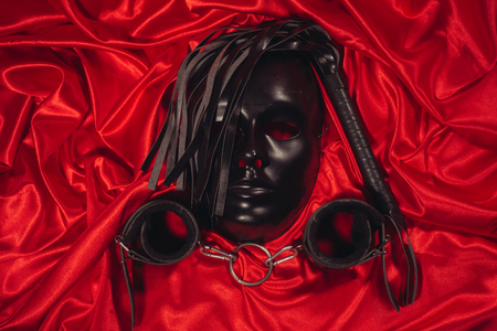 Bondage, kinky adult sex games, kink and BDSM lifestyle concept with a mask, pair of leather handcuffs, flogger, ball gag and a coller with a leash attached on red silk with copy space Banque d'images - 120558481