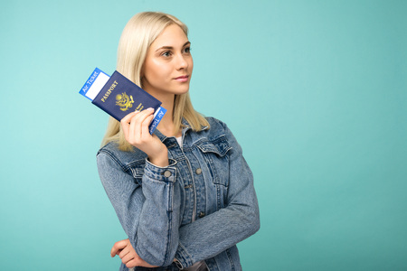 Dreamy girl in a denim jacket holds a passport with airline tickets - image