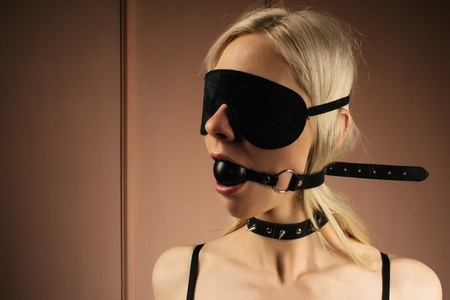 sexy lady in bdsm outfit. Close-up girl in mask and collar with gag in mouth -Image Zdjęcie Seryjne