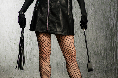 The dominant woman in a leather dress with a stack and a whip in her hand. Bdsm outfit - image Stock Photo