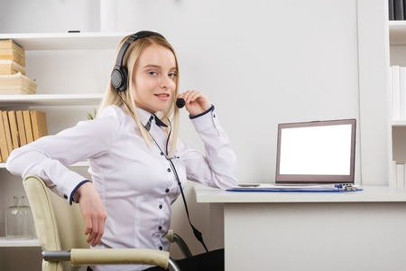 Portrait of happy smiling female customer support phone operator at workplace. - Image Stock fotó