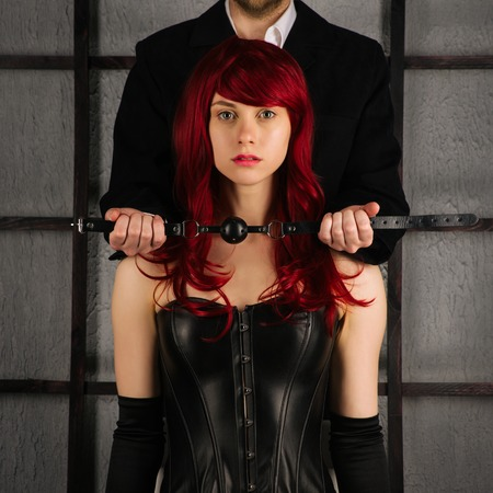 Adult games. A man holds a gag near the mouth of a red-haired girl in a leather corset. Bdsm outfit