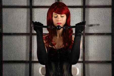 La ragazza dai capelli rossi in un corsetto di pelle tiene un bavaglio vicino alla bocca. Vestito sadomaso