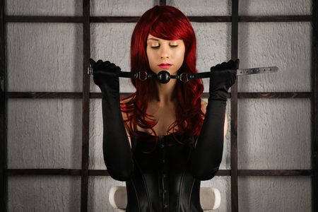 Red-haired girl in a leather corset holds a gag near the mouth. Bdsm outfit