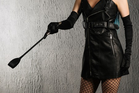 Dominant woman in a leather dress with a spank in hand. - image