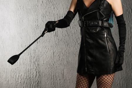 Femme dominante dans une robe en cuir avec une fessée à la main. - image Banque d'images