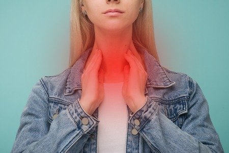 A young girl has a sore throat. Thyroid problems - Image 스톡 콘텐츠