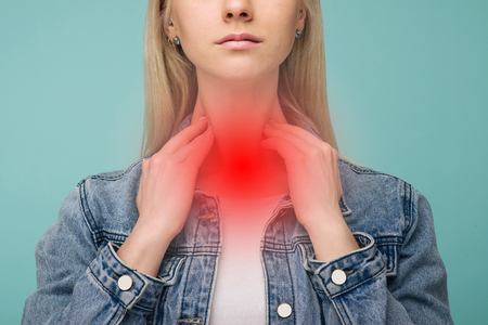 A young girl has a sore throat. Thyroid problems - Image Фото со стока